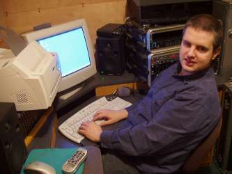 Picture of Phil smiling at a PC in his studio